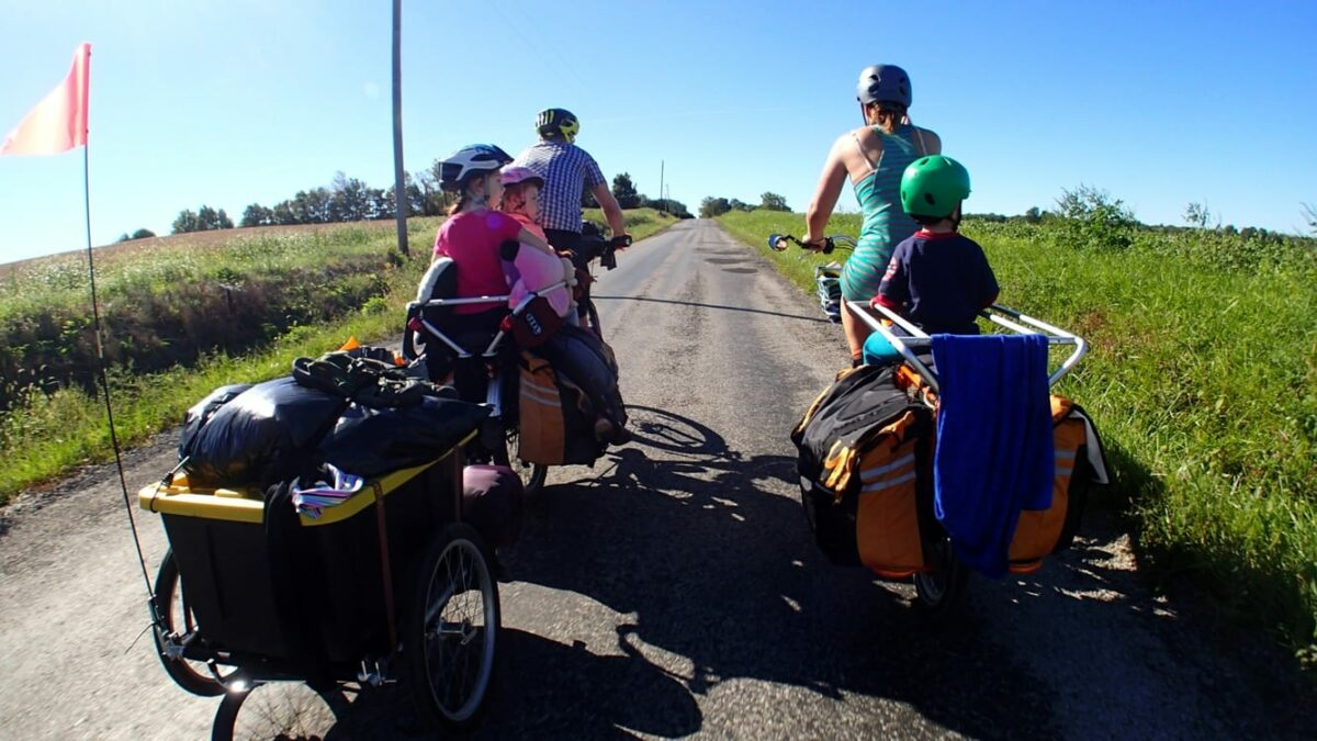 Family cycling towing camping gear.