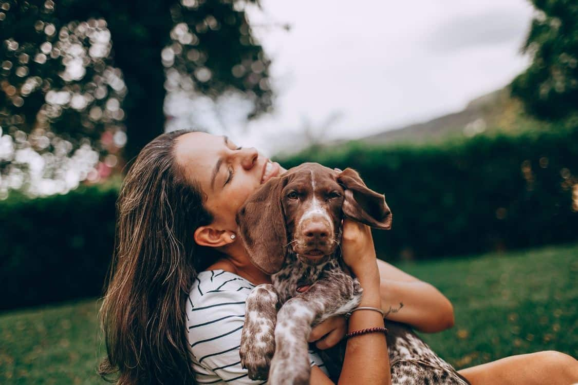 Woman in nature hugging her dog.