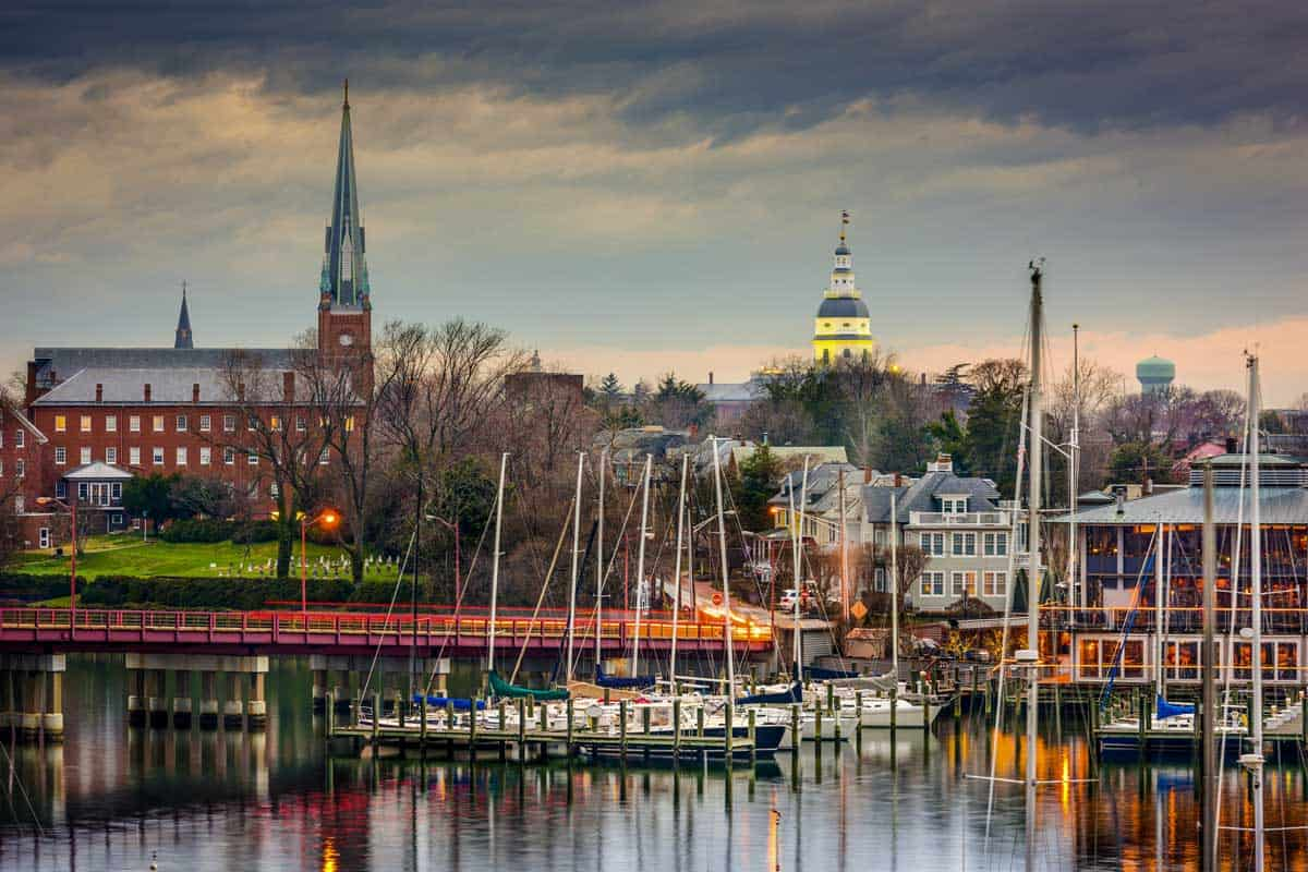 Annapolis skyline at sunset with yachts moored on the water.