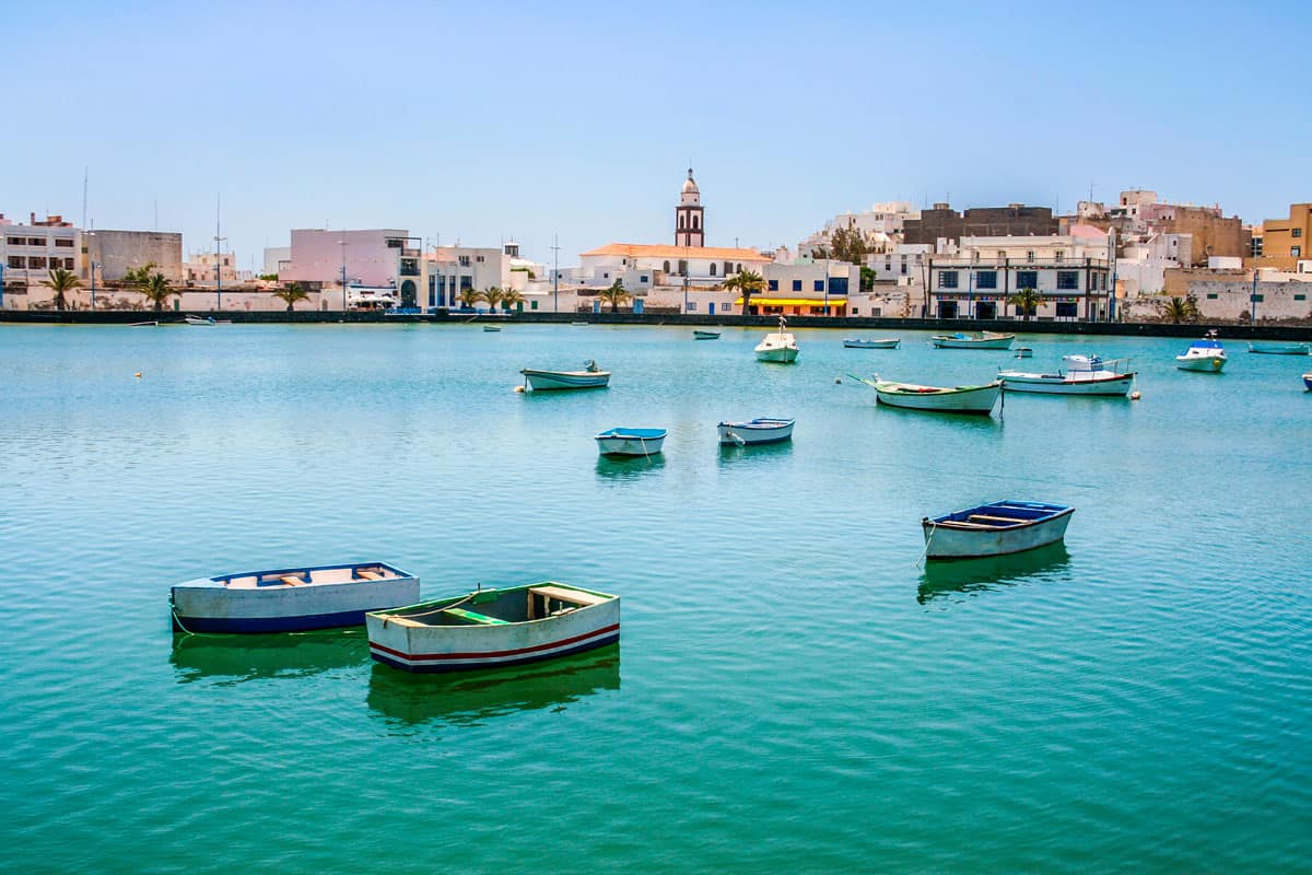 Row boats moored on turquoise water in Charco de San Gines Lanzarote island.