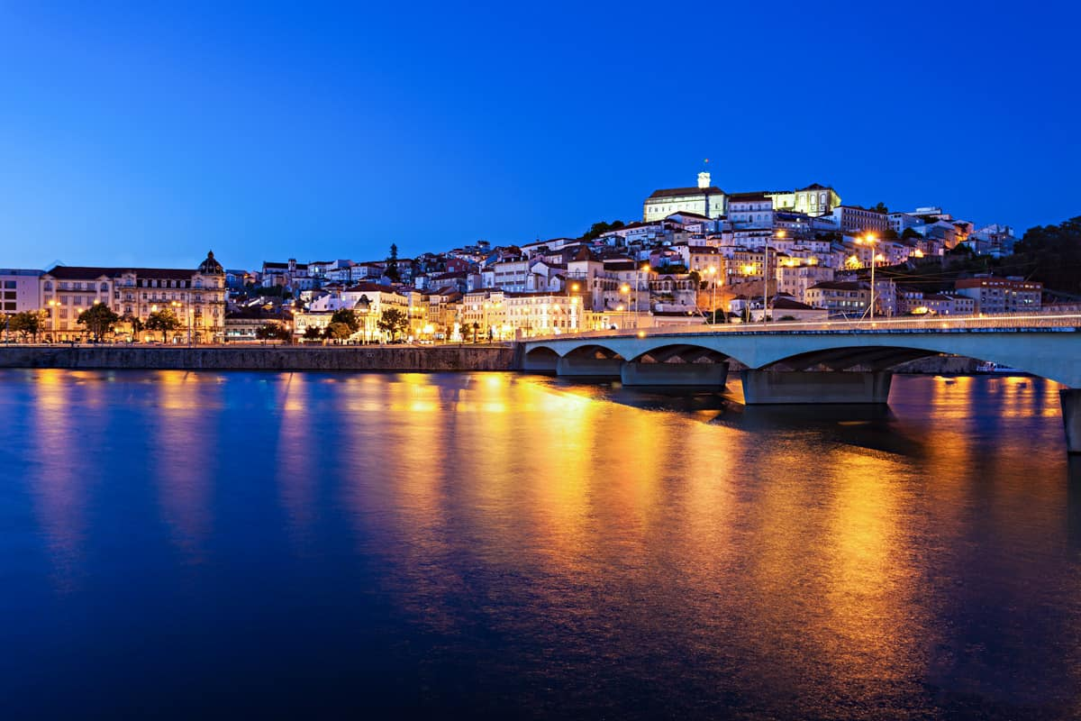 Coimbra city Portugal at night reflecting on the river.