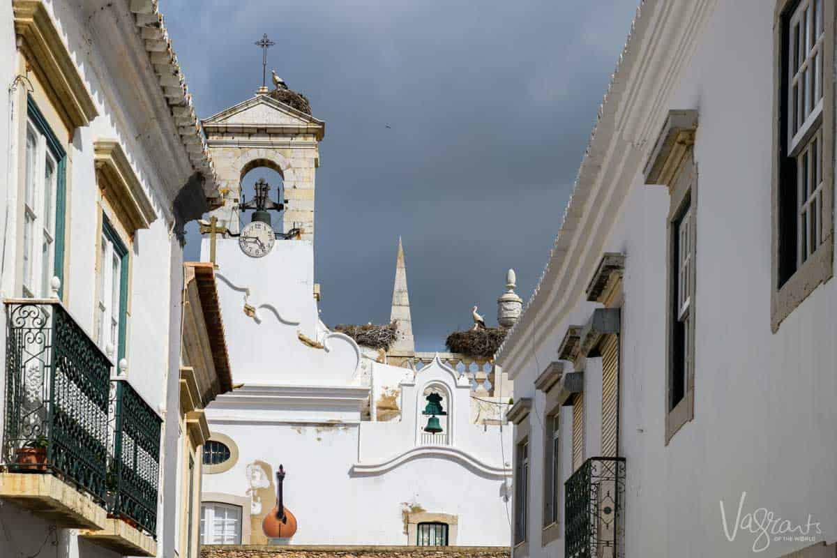 A church bell tower with storks nests in Faro Portugal.