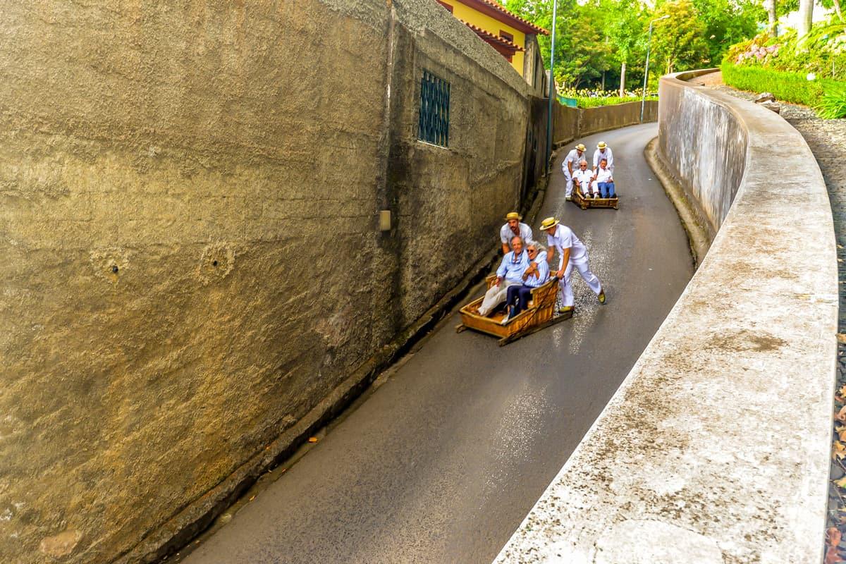 Tourists enjoying a traditional downhill toboggan ride on Madeira Island.