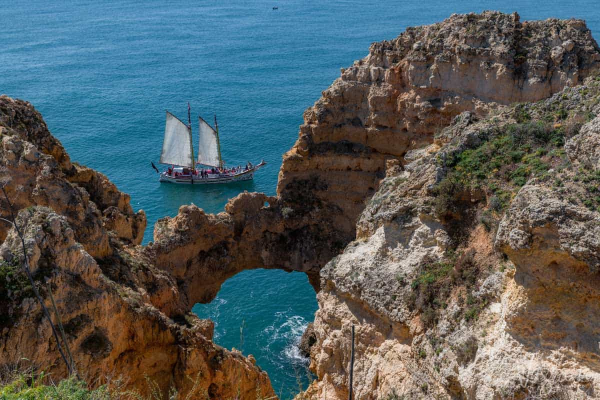 The cliffs of Lagos with a sailing oat cruising past under full sail.