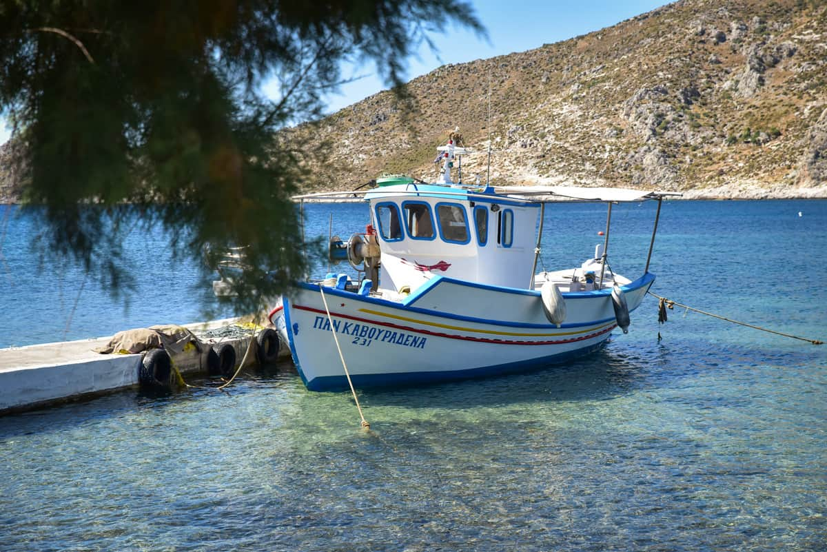 Typical Greek fishing boat tied up on crystal clear water on Leros Island