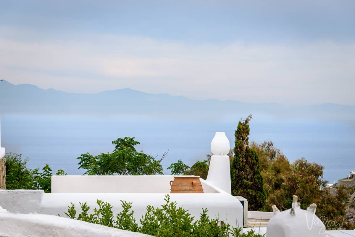 White painted terrace with terracotta pot overlooking the ocean in Mykonos.