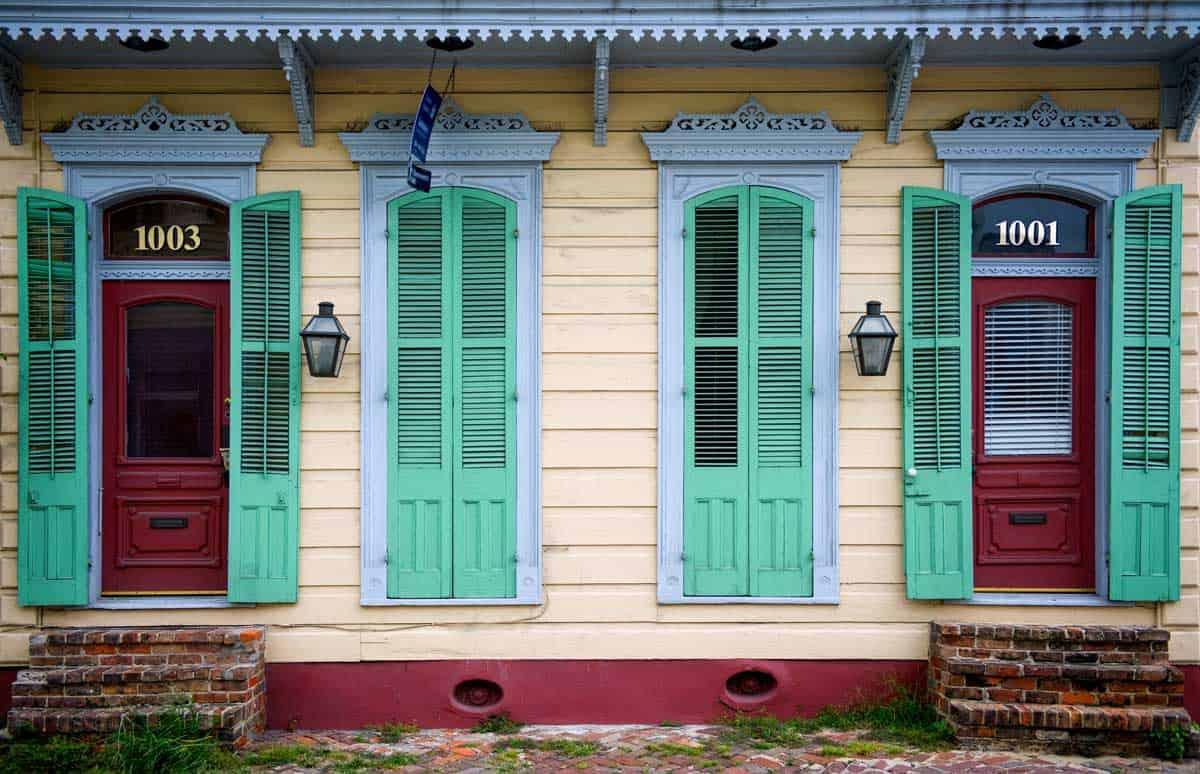 Typical New Orleans houses with green painted French doors.