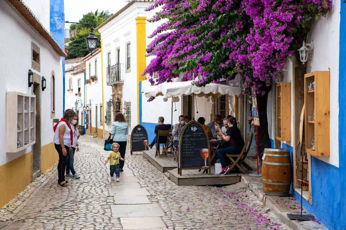 Cobblestone streets with colourful bougainvillea in Obidos Portugal.