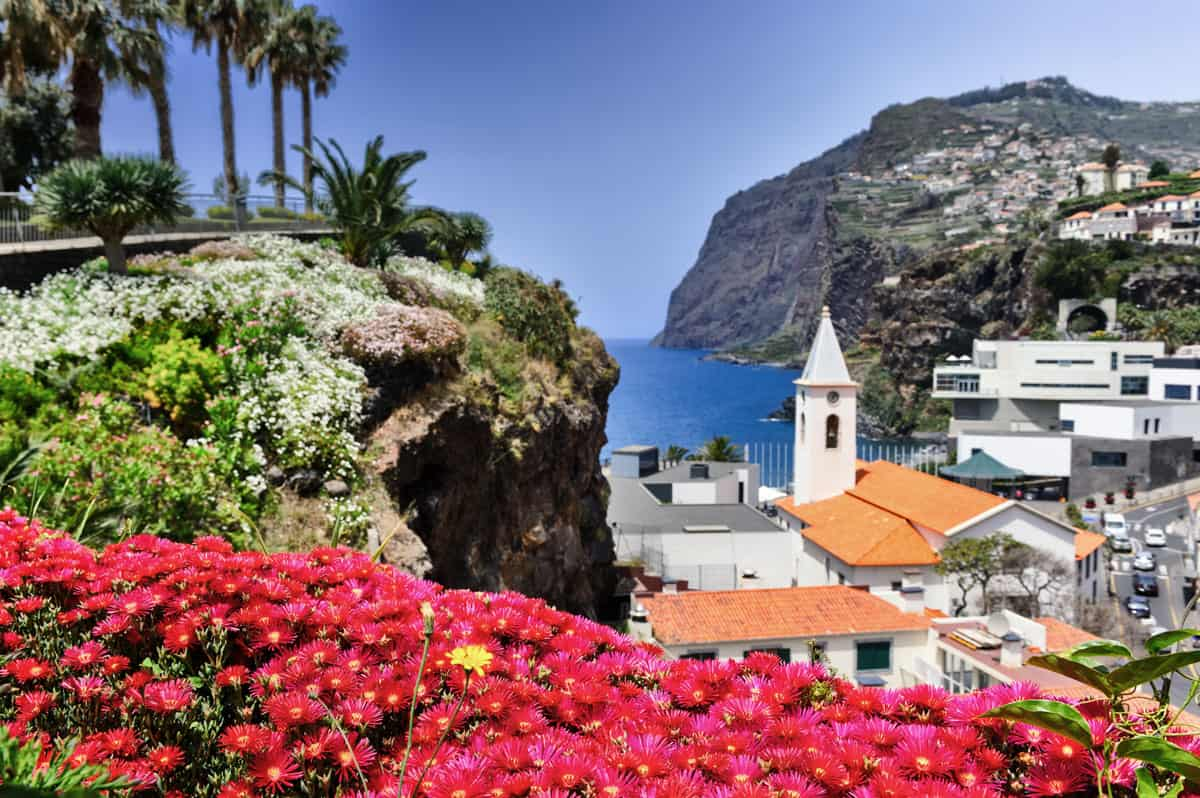 Bright flowers and a church spire overlooking the ocean in Madeira Island.