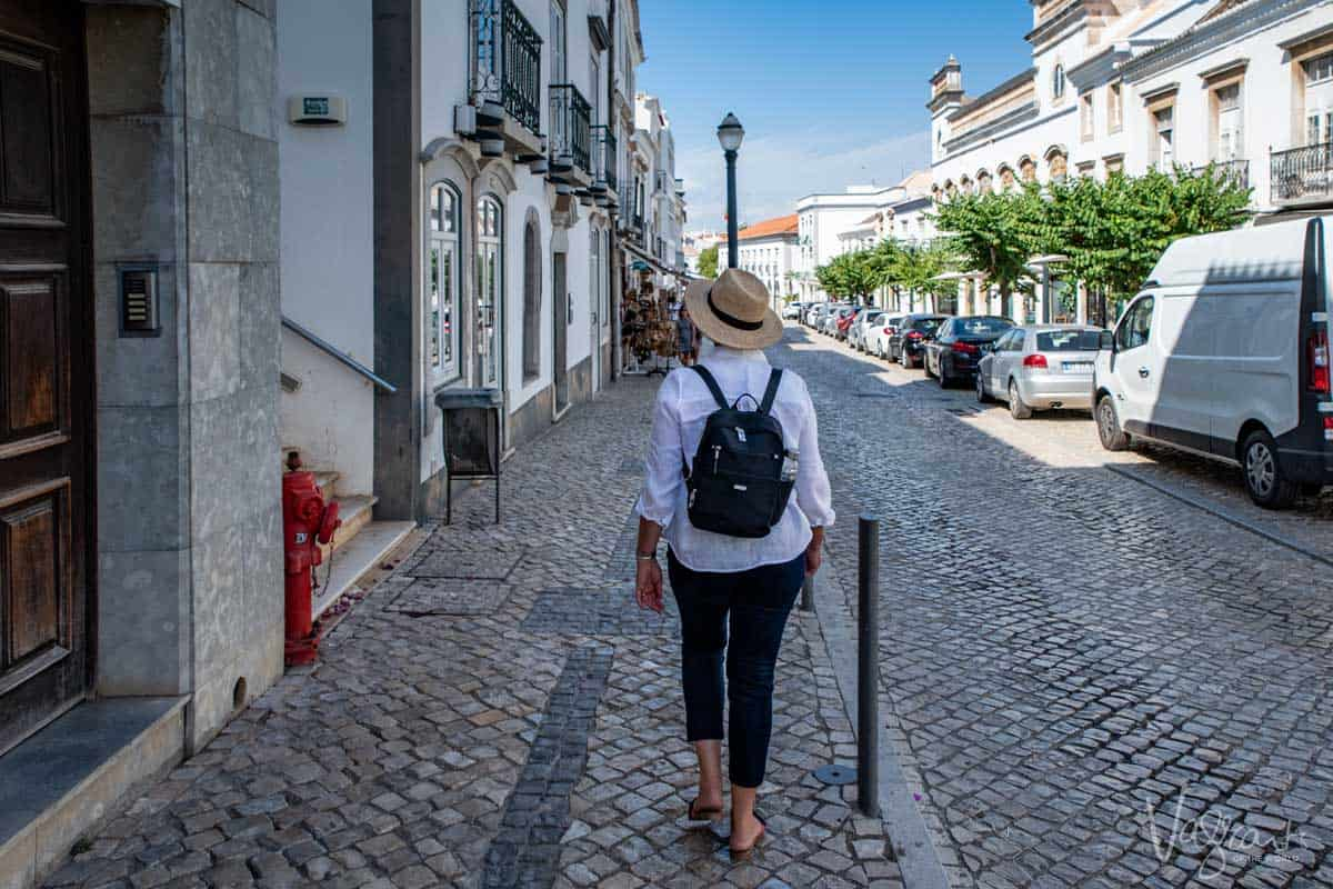 A woman walking down the quaint streets of Old Town Tavira in Portugal.