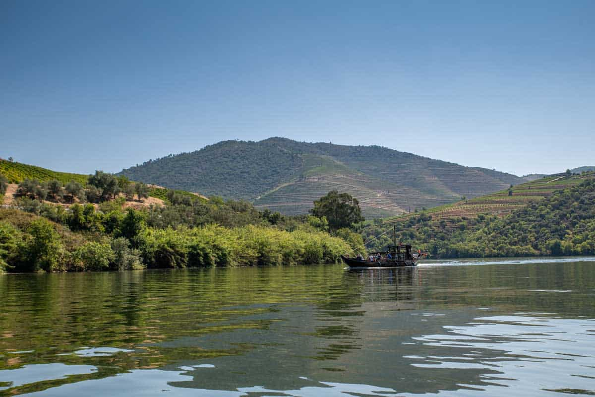 A traditional Rabelo boat cruising down the Douro river in Portugal.