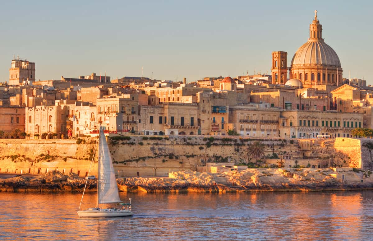 Saling boat travelling past the ancient city of Valletta in Malta.