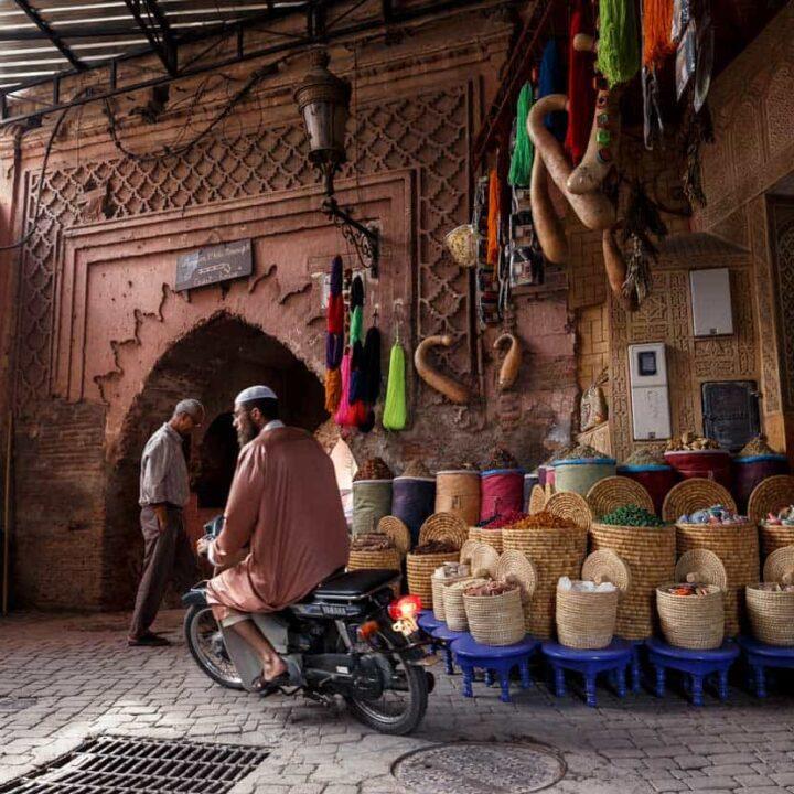 Islamic man riding a motorcycle through the Marrakech Medina.